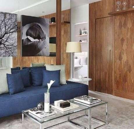 23. Sala chique com revestimento de madeira e sofá azul marinho – Foto Mariana Orsi
