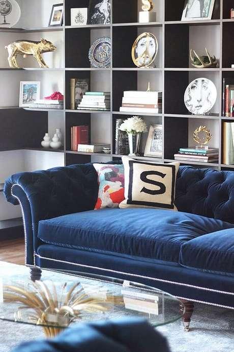 57. Sofá azul marinho na sala com estante cheia de enfeites – Foto Pinterest