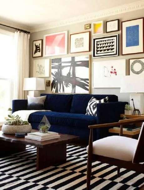31. Sala com sofá azul marinho e conjunto de quadros na parede – Foto Dimples and Tangles