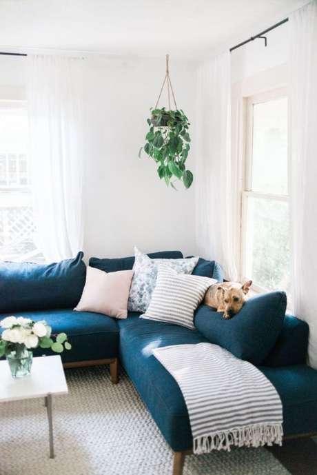 12. Sofá de canto azul marinho com manta e almofadas neutras – The Identité Collective