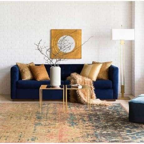 40. Sala moderna com sofá azul marinho e enfeites dourados – Foto Surya