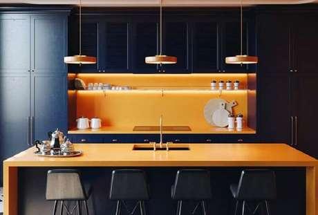 45. Decoração de cozinha preta com balcão no meio laranja – Foto: Pinterest