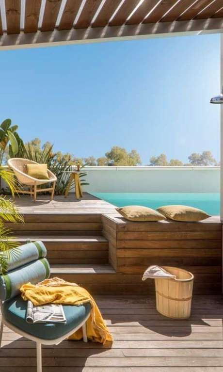4. Piscina elevada com deck de madeira e móveis confortáveis para tomar sol – Foto Pinterest