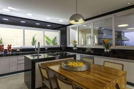 36. Decoração de cozinha com balcão no meio com mesa de madeira integrada – Foto: Iara Kilaris