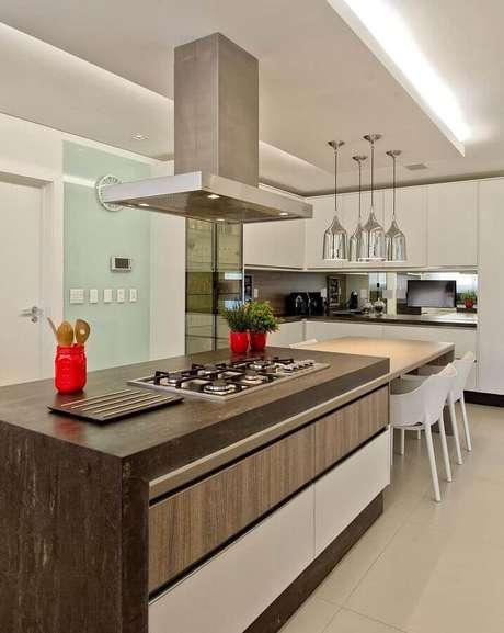 25. Decoração moderna em cozinha com balcão para cooktop planejado com mesa de madeira – Foto: Espaço do Traço