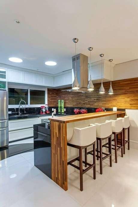 43. Decoração de cozinha planejada com balcão de granito preto e bancada de madeira – Foto: Decor Salteado