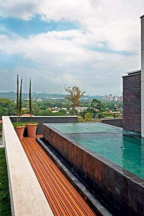 3. Piscina elevada com revestimento de pedra e plantas na decoração – Foto Pinterest