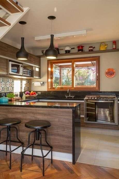 34. Decoração de cozinha com balcão em U planejada com armários de madeira – Foto: Lore Arquitetura