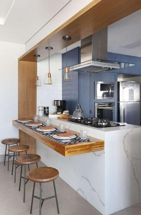 21. Cozinha com balcão de mármore planejado com cooktop e decorada com bancada de madeira – Foto: Pinterest