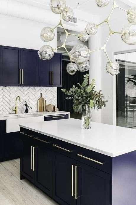 54. Decoração sofisticada com lustre moderno e armário azul marinho para cozinha com balcão no meio – Foto: Pinterest