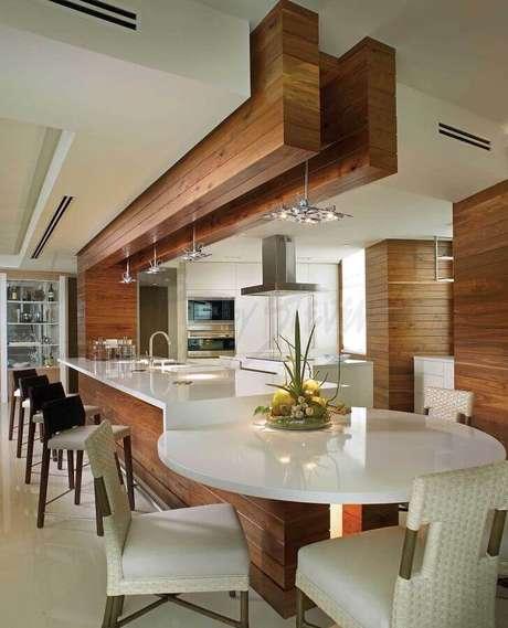 31. Decoração de cozinha com balcão branco planejado com mesa redonda – Foto: Steven Gambriel Arquitetura