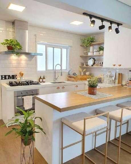 20. Cozinha com balcão de madeira decorada com armários brancos – Foto: Pinterest