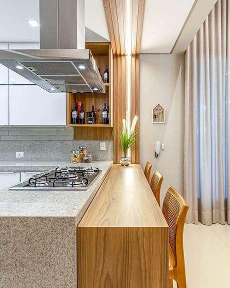 9. Decoração de cozinha com balcão de granito com cooktop e bancada de madeira – Foto: Decor Salteado