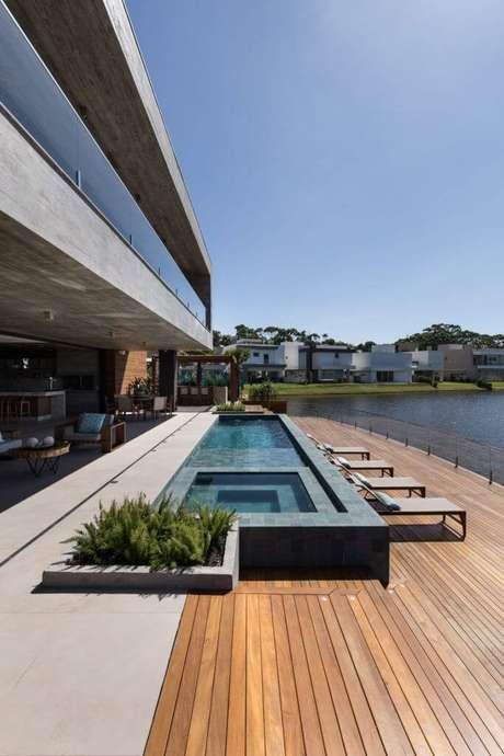 59. Piscina com revestimento de pedra preta e deck de madeira – Foto Martin Arquitetura + Engenharia