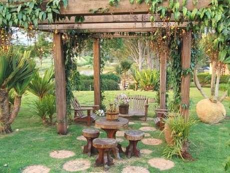 80. Crie um ambiente especial no jardim da casa de fazenda com pergolado e móveis de madeira. Fonte: Pinterest