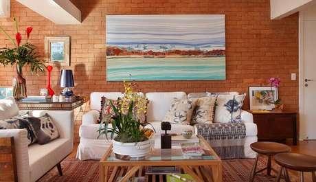 37. Decoração de sala com parede de tijolinho a vista e quadro grande – Foto: Escala Arquitetura