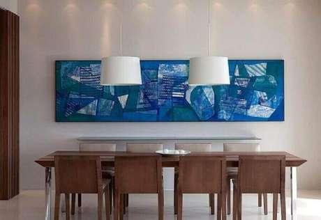 35. Quadro grande azul para decoração de sala de jantar com cadeiras de madeira – Foto: Patrícia Martinez Arquitetura