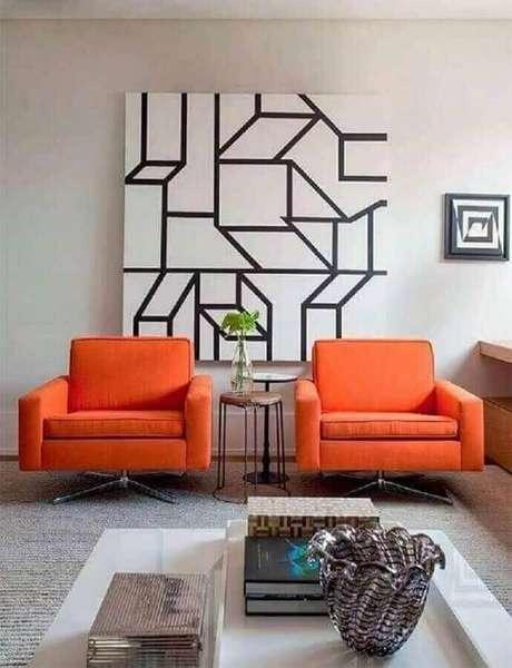55. Decoração de sala de estar com poltrona laranja e quadro abstrato grande – Foto: Pinterest