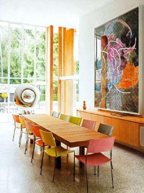 28. Quadros grandes para sala de jantar decorada com mesa de madeira e cadeiras coloridas – Foto: Arkpad