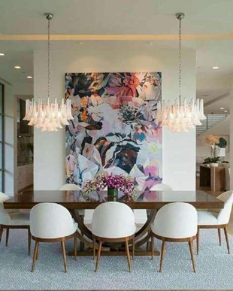 12. Decoração com lustre moderno e quadros grandes para sala de jantar – Foto: Pinterest