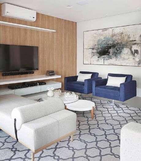 27. Quadro grande para sala de TV decorada com poltronas azuis – Foto: Pinterest