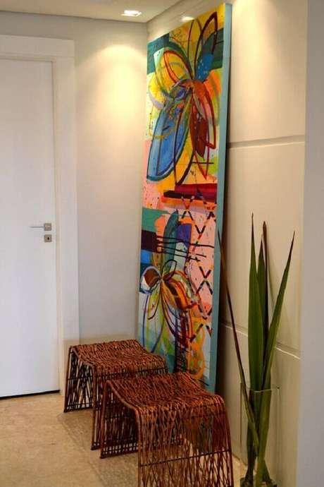 31. Quadro grande colorido para decoração de hall com bancos rústicos – Foto: Homify