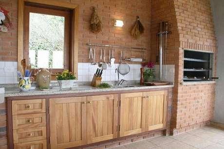 78. Cozinha com móveis rústicos e churrasqueira de tijolinhos. Fonte: Pinterest
