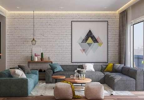 43. Quadro grande para sala de estar decorada com parede de tijolinho branco – Foto: Pinterest