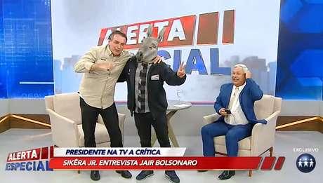 Bolsonaro faz graça ao lado do assistente de estúdio fantasiado de jumento no 'Alerta Especial' de Sikêra Jr.