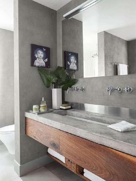 27. Bancada de cimento queimado banheiro com elementos em madeira. Fonte: Conexão Décor