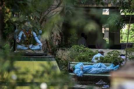 Um familiar exausto antes de realizar os últimos ritos para vítimas da covid em um campo de cremação em Vasai, nos arredores de Mumbai, Índia