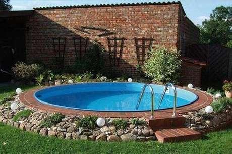 20. Pedras, plantas e tijolos decoram o entorno da piscina de fibra redonda. Fonte: Arkpad