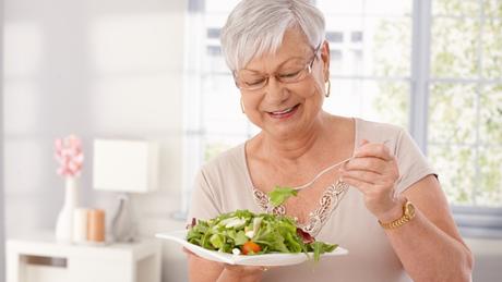 Senhora comendo salada