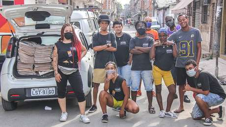 Jovens moradores da Maré circulam pela favela levando jornal feito pela comunidade, com dados sobre infecções por covid e informações sobre prevenção