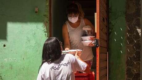 Volutários do Conexão Saúde, a maioria moradores da favela, entregam alimentos diariamente para quem está se isolando em casa