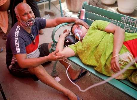 Homem ao lado da esposa que recebe suporte de oxigênio do lado de fora de templo em Ghaziabad, na Índia 03/05/2021 REUTERS/Adnan Abidi