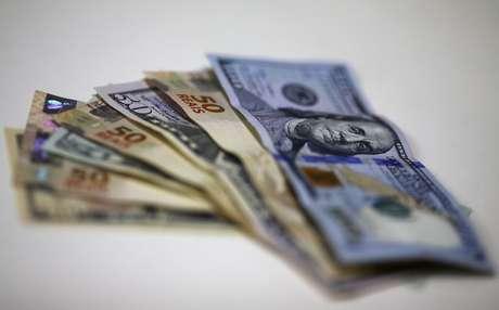 Notas do dólar e do real são dispostas em corretora de câmbio. 10/09/2015. REUTERS/Ricardo Moraes.