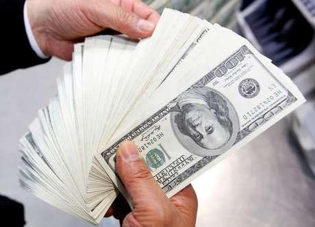 Funcionário do banco Korea Exchange conta cédulas de cem dólares na sede da instituição em Seul 28/04/2010 REUTERS/Jo Yong-Hak