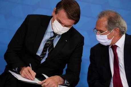 O presidente Jair Bolsonaro fala com o ministro da Economia, Paulo Guedes. 25/03/2021. REUTERS/Ueslei Marcelino.