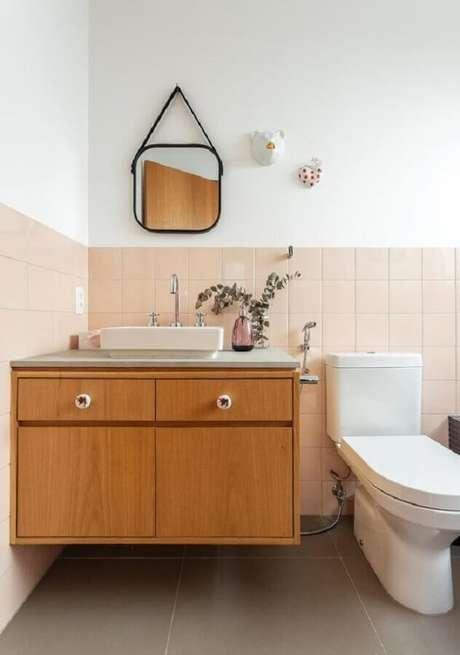 58. Revestimento meia parede rosa claro para decoração de banheiro com gabinete suspenso – Foto: Histórias de Casa