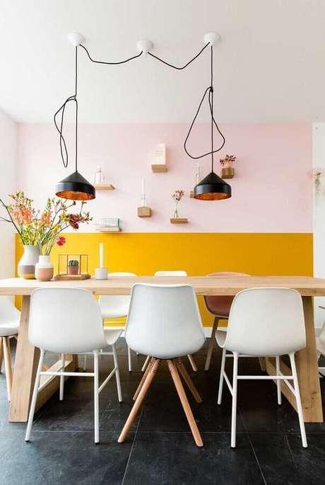 31. Pintura meia parede amarela para sala de jantar decorada com mesa de madeira e luminária pendente preta – Foto: Pinterest