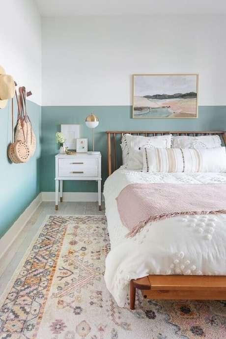 33. Decoração de quarto de casal com cama de madeira e meia parede pintada de azul claro – Foto: Apartment Therapy