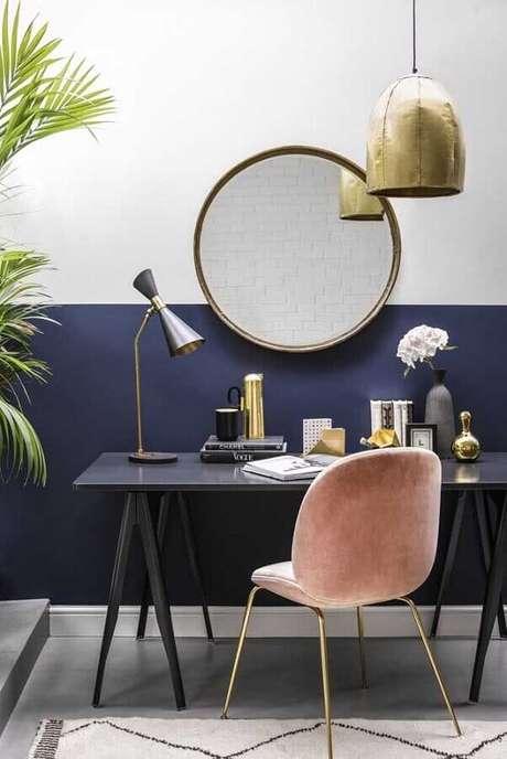 30. Home office decorado com escrivaninha preta e meia parede azul marinho – Foto: Home Fashion Trend
