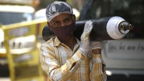 Uma pessoa esperando para reabastecer seu cilindro de oxigênio vazio em Gurgaon, Índia; cena aconteceu tanto no Brasil quanto no pais asiático