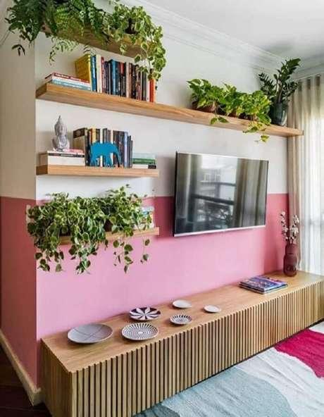 47. Pintura meia parede cor de rosa para sala de TV decorada com prateleiras e rack de madeira – Foto: Jeito de Casa