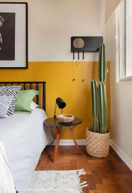 50. Decoração meia parede amarela para quarto com cabeceira preta e vaso de chão – Foto: Histórias de Casa