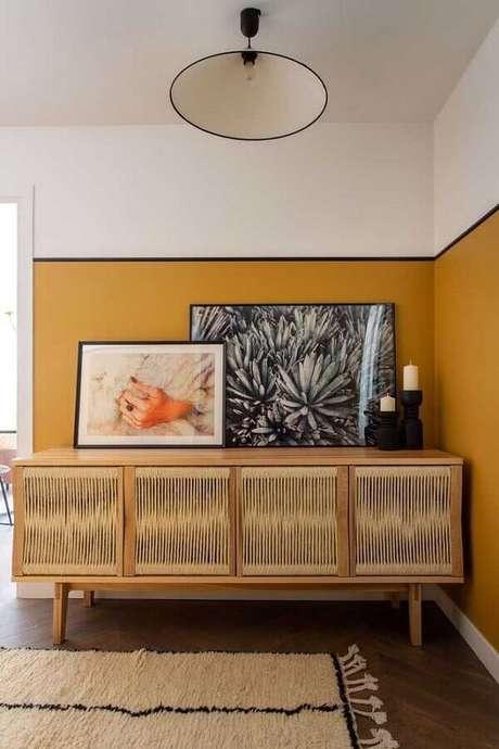 39. Meia parede mostarda para decoração de sala com buffet de madeira – Foto: Pinterest