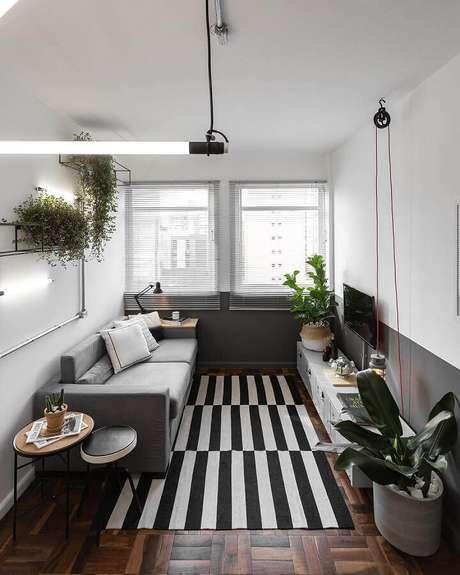 41. Decoração para sala de estar com tapete listrado e meia parede cinza e branca – Foto: Jeito de Casa