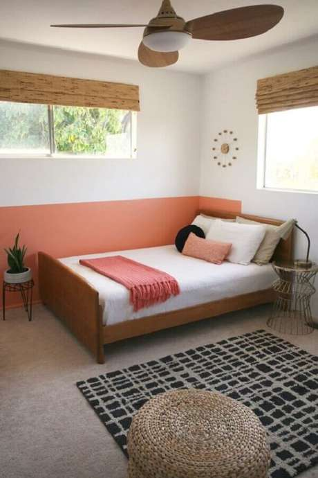52. Quarto simples decorado com cama de madeira e meia parede rosa – Foto: Pinterest