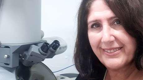 A bióloga e professora da FMUSP Elia Caldini. Ao fundo, o microscópio eletrônico, que aumenta dezenas de milhares de vezes as amostras de tecido para que os patologistas vejam o Sars-CoV-2
